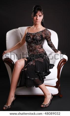 beautiful brunette sitting on white armchair - stock photo