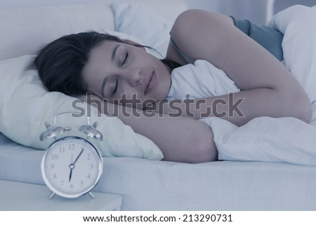 Beautiful brunette sleeping in her bed at home in the bedroom - stock photo