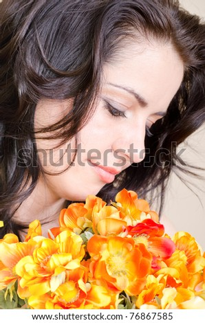 Beautiful brunette smell flowers - stock photo