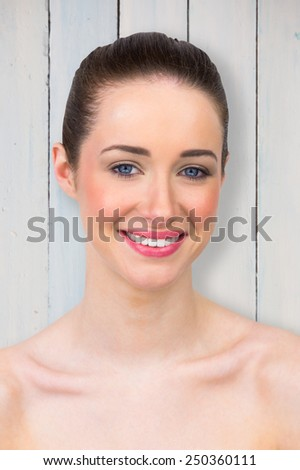 Beautiful brunette smiling at camera against painted blue wooden planks - stock photo