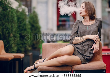 beautiful brunette smoke electronic cigarette on the summer terrace of restaurant - stock photo