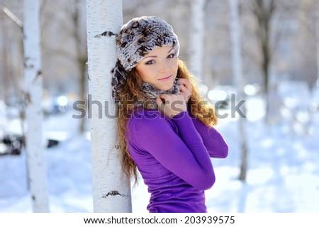 beautiful brunette standing near birch in winter - stock photo