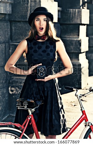 Beautiful brunette standing near her old bicycle and holding the old camera over city background. Retro style.