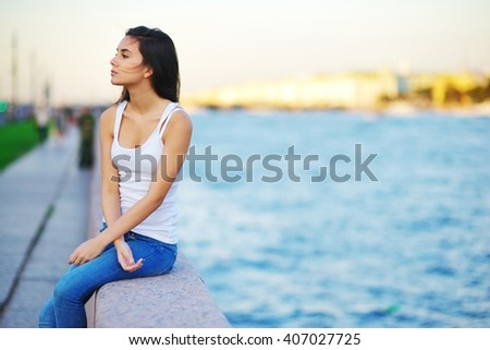 beautiful brunette student girl in blue jeans and white shirt sitting on the embankment near the river - stock photo