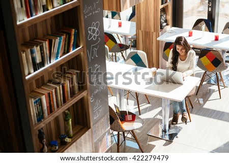 Beautiful brunette studying on notebook - stock photo