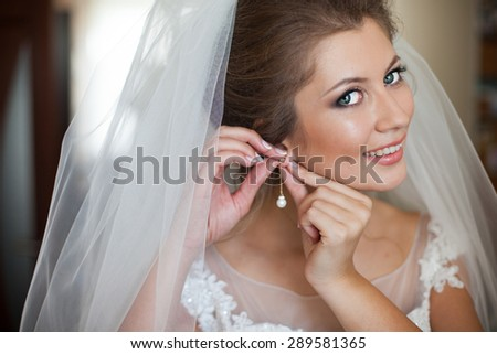 beautiful brunette stylish bride getting ready in the morning in the room - stock photo
