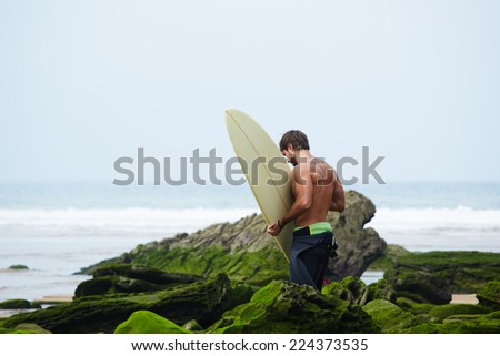 Beautiful brunette surfer walks on moss rocks carrying surfboard, sexy surfer man with muscular body going to surfing on big waves - stock photo