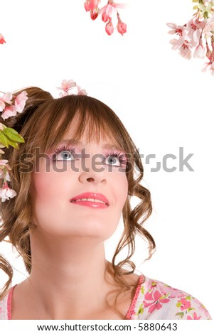 Beautiful brunette surrounded by spring flowers on white background