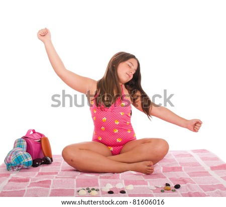 beautiful brunette teenage girl in swimsuit at the beach relaxing with arms raised (studio setting with cap, towel, bag, sun lotion, sunglasses and stones) isolated on white background - stock photo