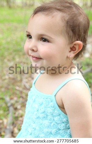 Beautiful brunette toddler girl playing outside in the field - stock photo