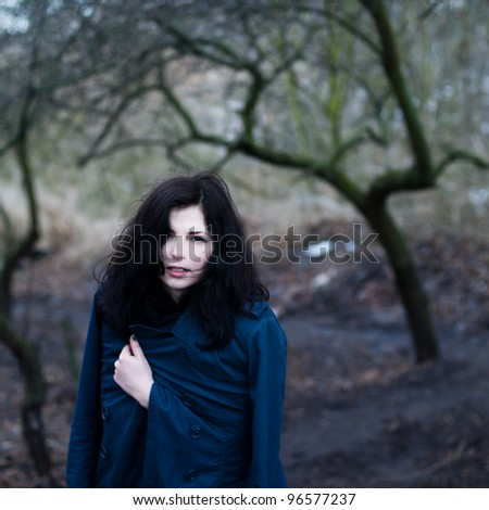 Beautiful brunette warms in spring park