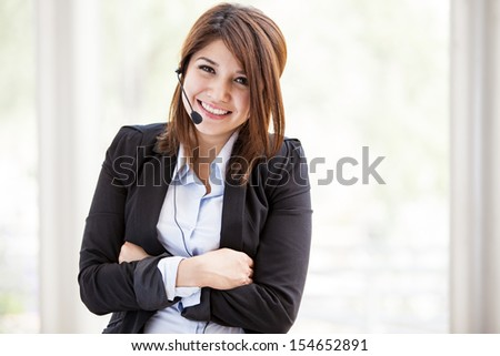 Beautiful brunette wearing a suit and a headset ready to take your customer service call with a smile - stock photo