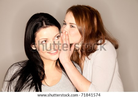 beautiful brunette whispering something into the ear of her girlfriend - stock photo