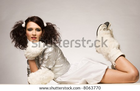 beautiful brunette winter girl wearing furry gloves and boots and white dress on light background