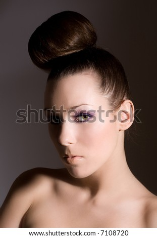 Beautiful brunette with a fashionable hairstyle and purple eye shadow - stock photo