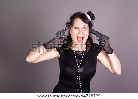 Beautiful brunette with a gun in the form of a gangster, studio shot - stock photo