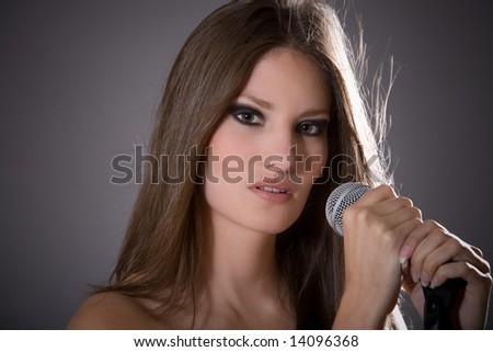 Beautiful brunette with a microphone in front of her