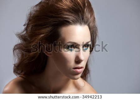 Beautiful brunette with a wild hairstyle looking intense - stock photo