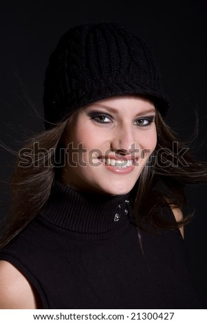 Beautiful brunette with a winter hat on on black background with gorgeous smile - stock photo