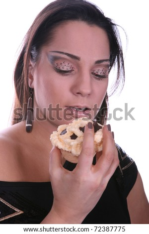 Beautiful brunette with artistic makeup eating a muffin - stock photo