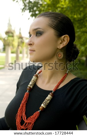 Beautiful brunette with black top and long red necklace sitting on a park bench - stock photo