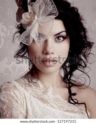 Beautiful brunette with curly hair wearing a hat - stock photo