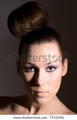 Beautiful brunette with fashionable hairstyle and purple eye shadow - stock photo