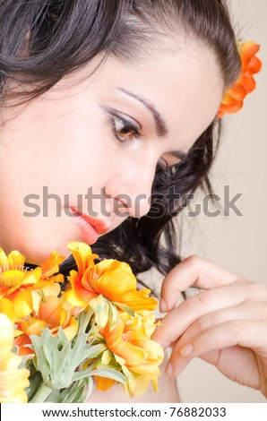 Beautiful brunette with flowers sadly looking - stock photo