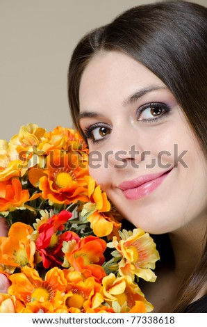 Beautiful brunette with flowers smiling - stock photo