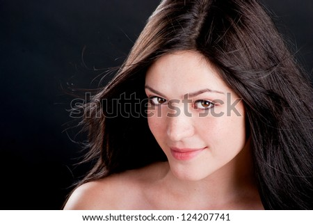 Beautiful brunette with freckles on a black background - stock photo
