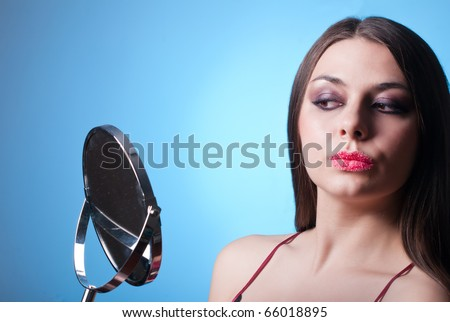 Beautiful brunette with gold eye shadow and sugar lips looking at mirror on blue background - stock photo