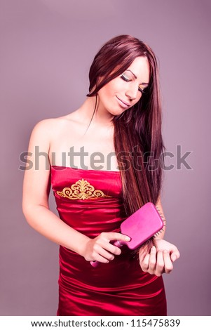 Beautiful brunette with hair comb - stock photo