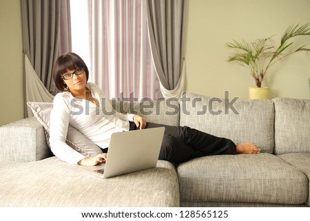 beautiful brunette with laptop on sofa