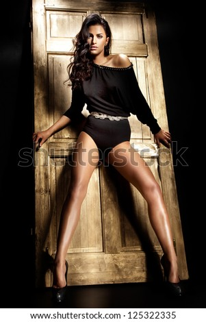 Beautiful brunette with long tanned legs posing over the gold background - stock photo