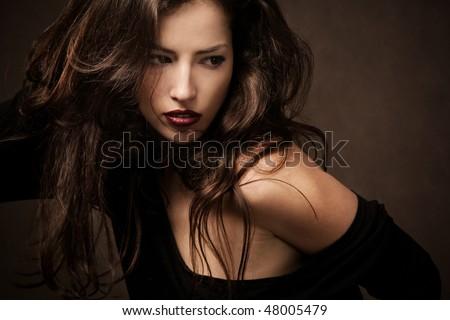 beautiful brunette with long wild hair portrait, studio shot - stock photo