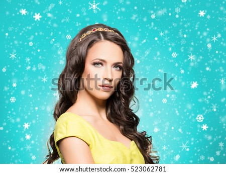 Beautiful brunette with luxury golden necklace over cyan winter background. Christmas concept.