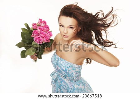 beautiful brunette with pink roses and wind blow hair - stock photo