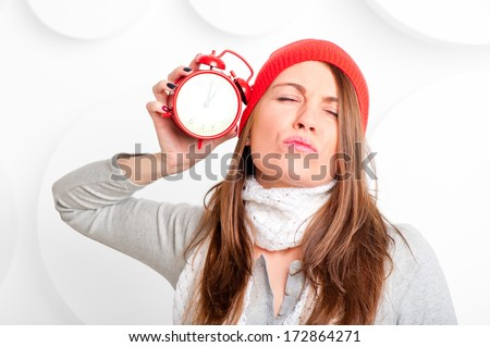 beautiful brunette with red alarm clock in the studio - stock photo