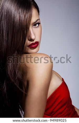 beautiful brunette with red lips and dress, studio portrait - stock photo