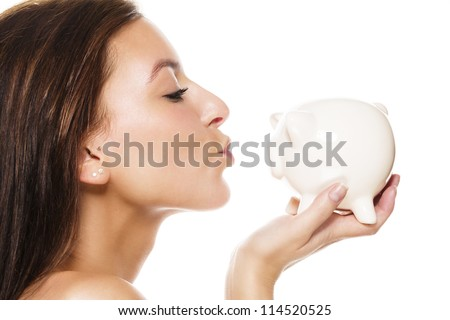beautiful brunette woman about to kiss a white piggy bank on white background - stock photo