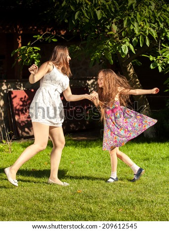 Beautiful brunette woman an young girl holding ands and dancing at yard - stock photo