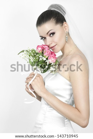 Beautiful brunette woman as bride with roses bouquet - stock photo