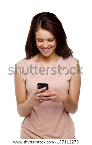Beautiful brunette woman casually dressed isolated on a white background using a mobile phone