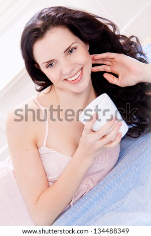beautiful brunette woman drinking coffee in bed morning sunshine - stock photo