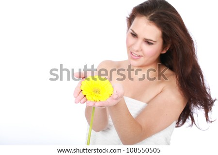 Beautiful brunette woman enjoying a day at the spa with white towel and yellow aromatic Gerber flower isolated on white background - stock photo