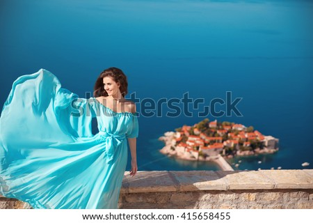 Beautiful brunette woman enjoying over blue sea. Girl in blowing wind dress. Summer holiadays. Sveti Stefan, Montenegro. Outdoor fashion portrait. - stock photo