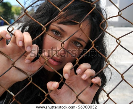Beautiful brunette woman grasping onto the links of a chain fence trapped in the city. - stock photo