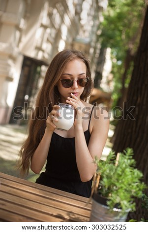 Beautiful brunette woman having a cold coffee drink. - stock photo