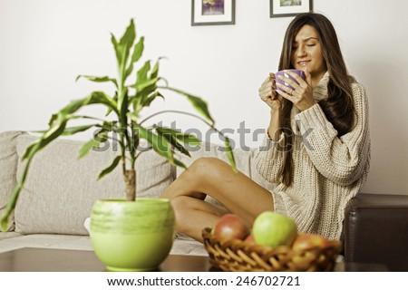 Beautiful brunette woman having her morning coffee - stock photo