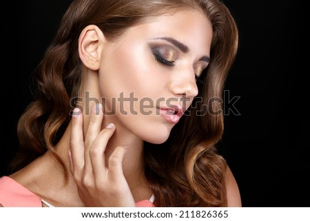 Beautiful brunette woman in a pink dress with wavy hairstyle eyes closed on black background - stock photo
